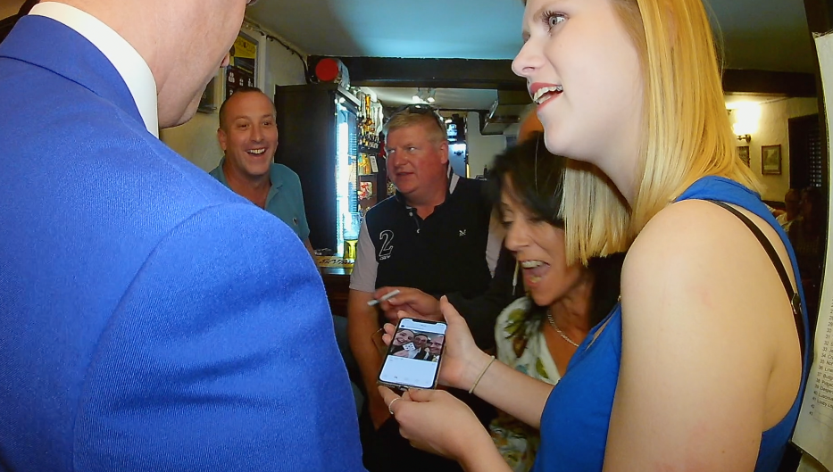woman with phone and wedding magician at teenage cancer trust fundraiser